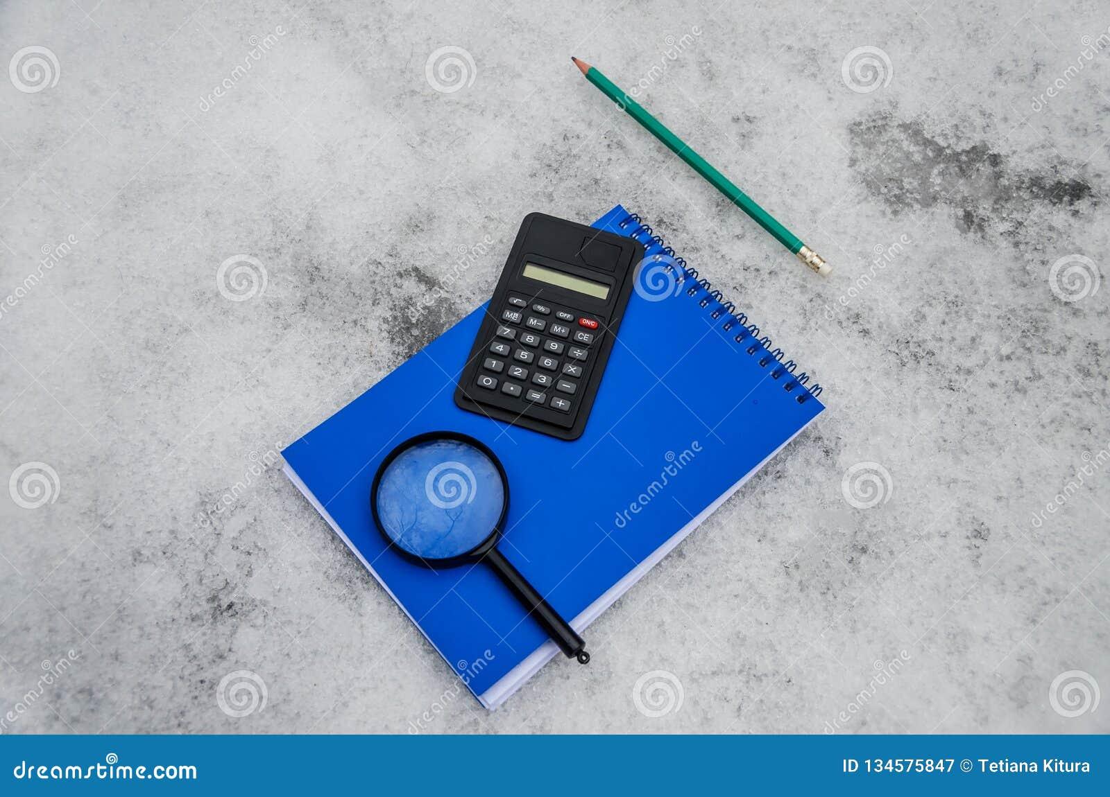 Голубой блокнот, калькулятор, увеличитель и зеленый карандаш на белой предпосылке снега