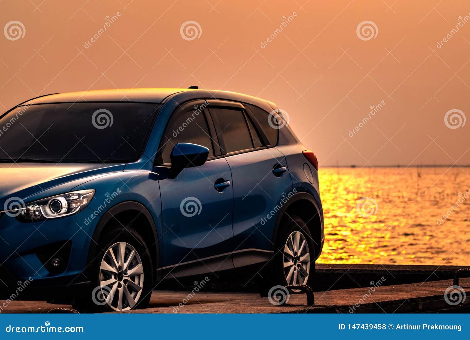 Голубой компактный автомобиль SUV со спортом и современным дизайном припаркованный на конкретной дороге морским путем на заходе с