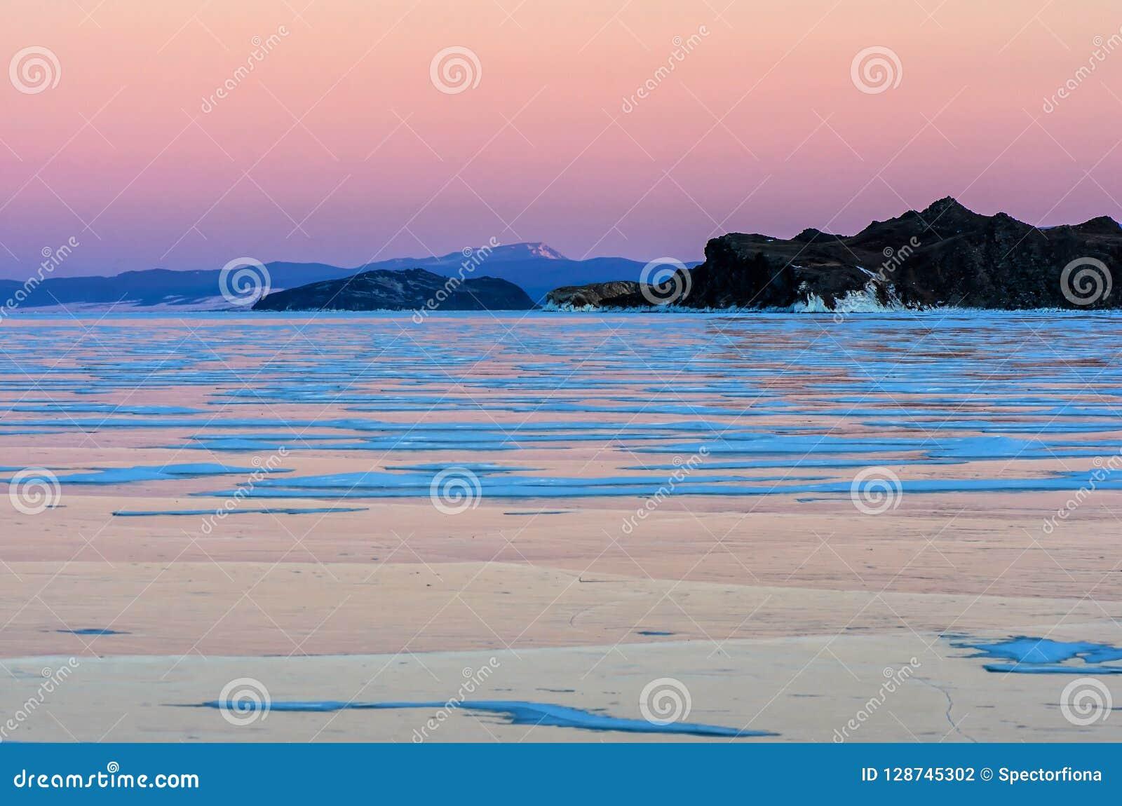 Голубой лед озера Байкал под розовым небом захода солнца