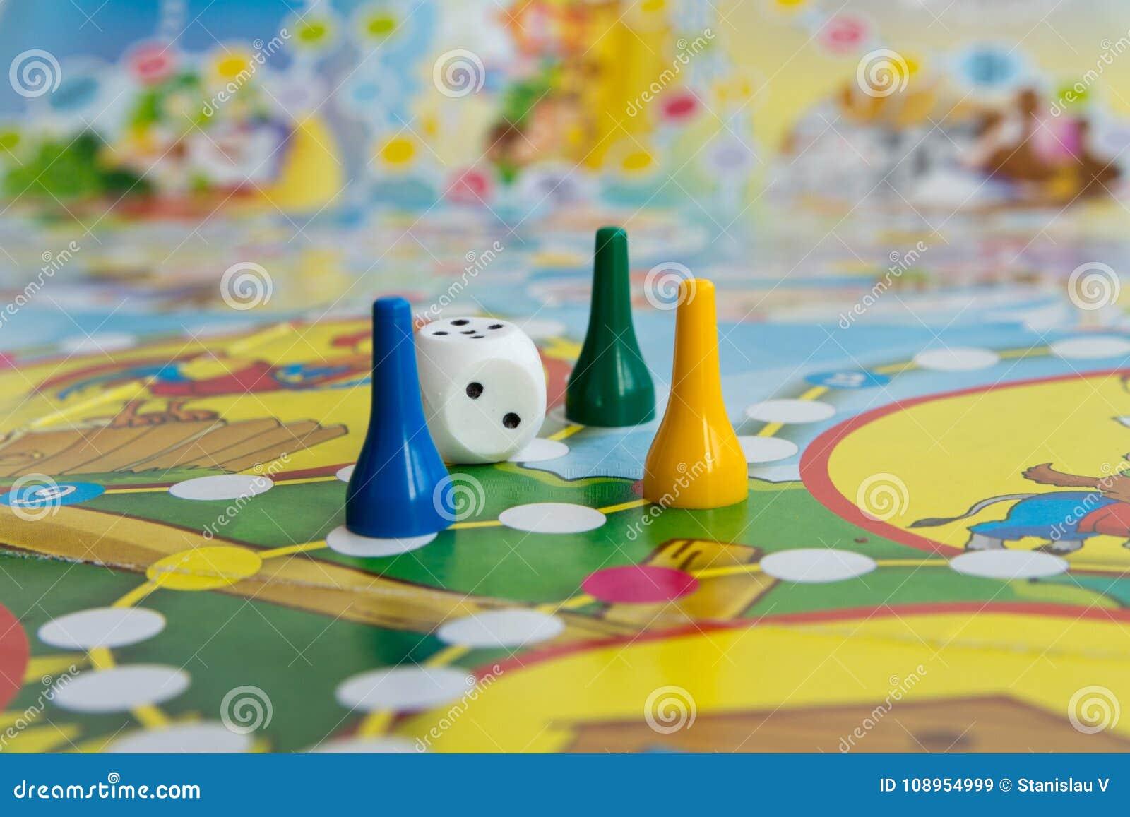 Голубые, желтые и зеленые пластичные обломоки, кость и настольные игры для детей