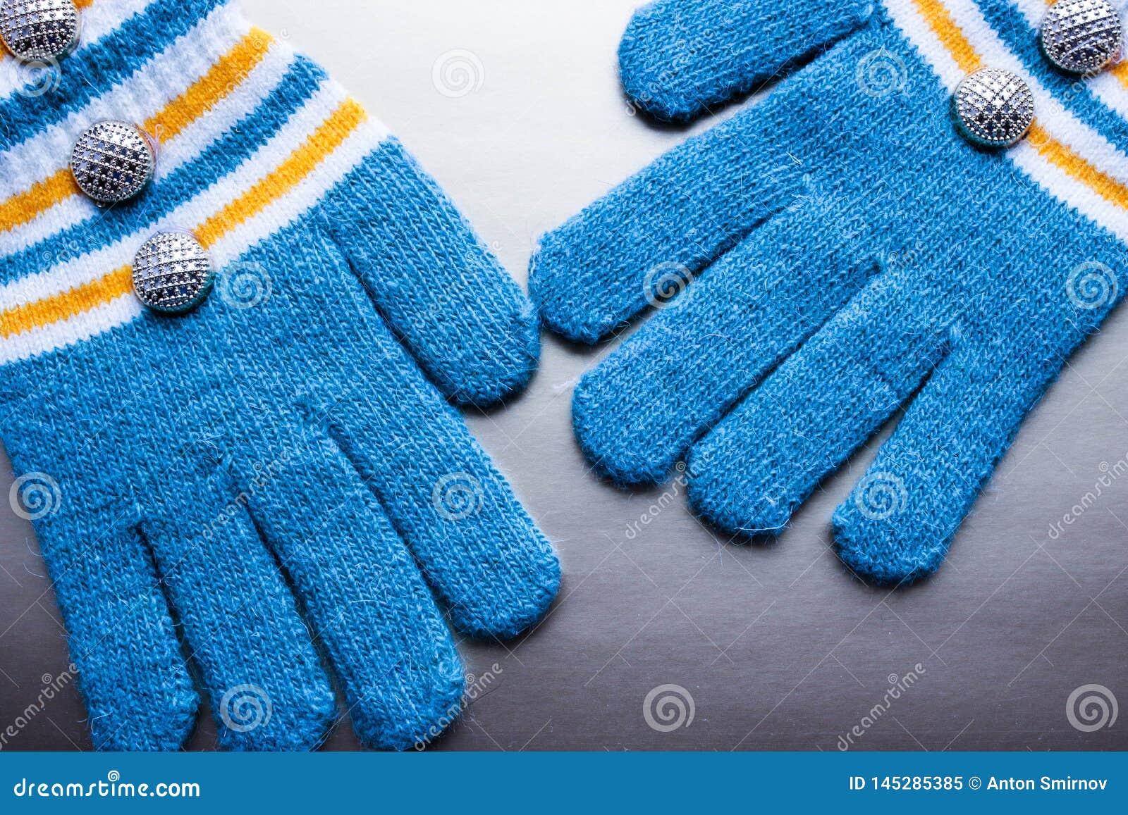 Голубые связанные mittens на пурпурной предпосылке