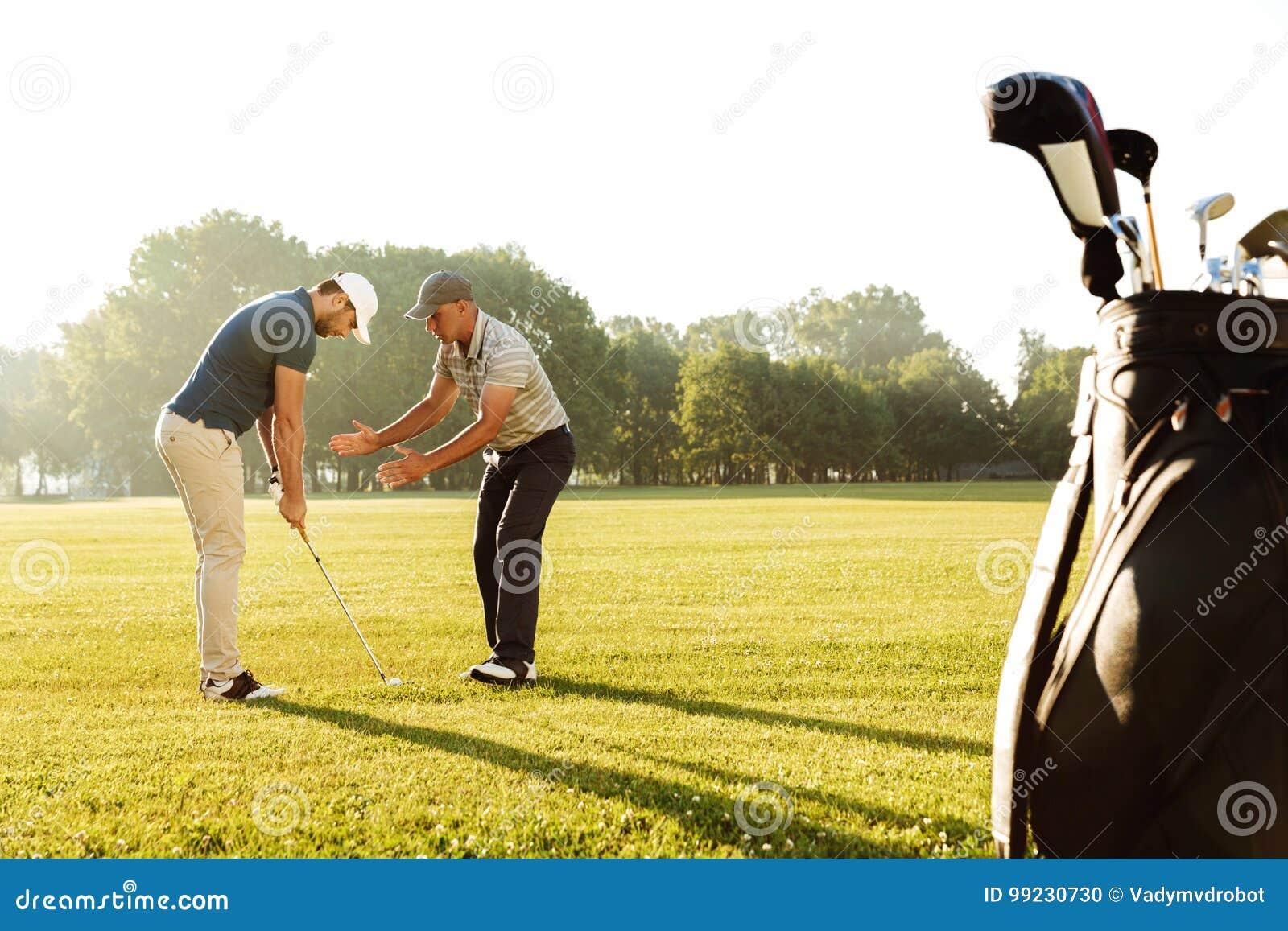 Гольф молодого спортсмена практикуя с его учителем