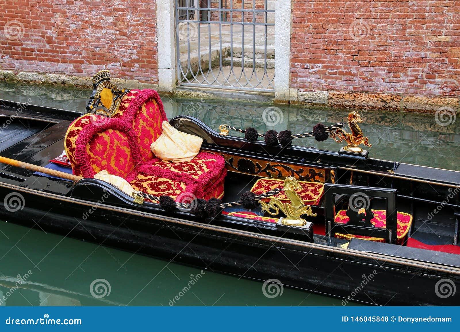 Гондола причаленная в узком канале в Венеции, Италии