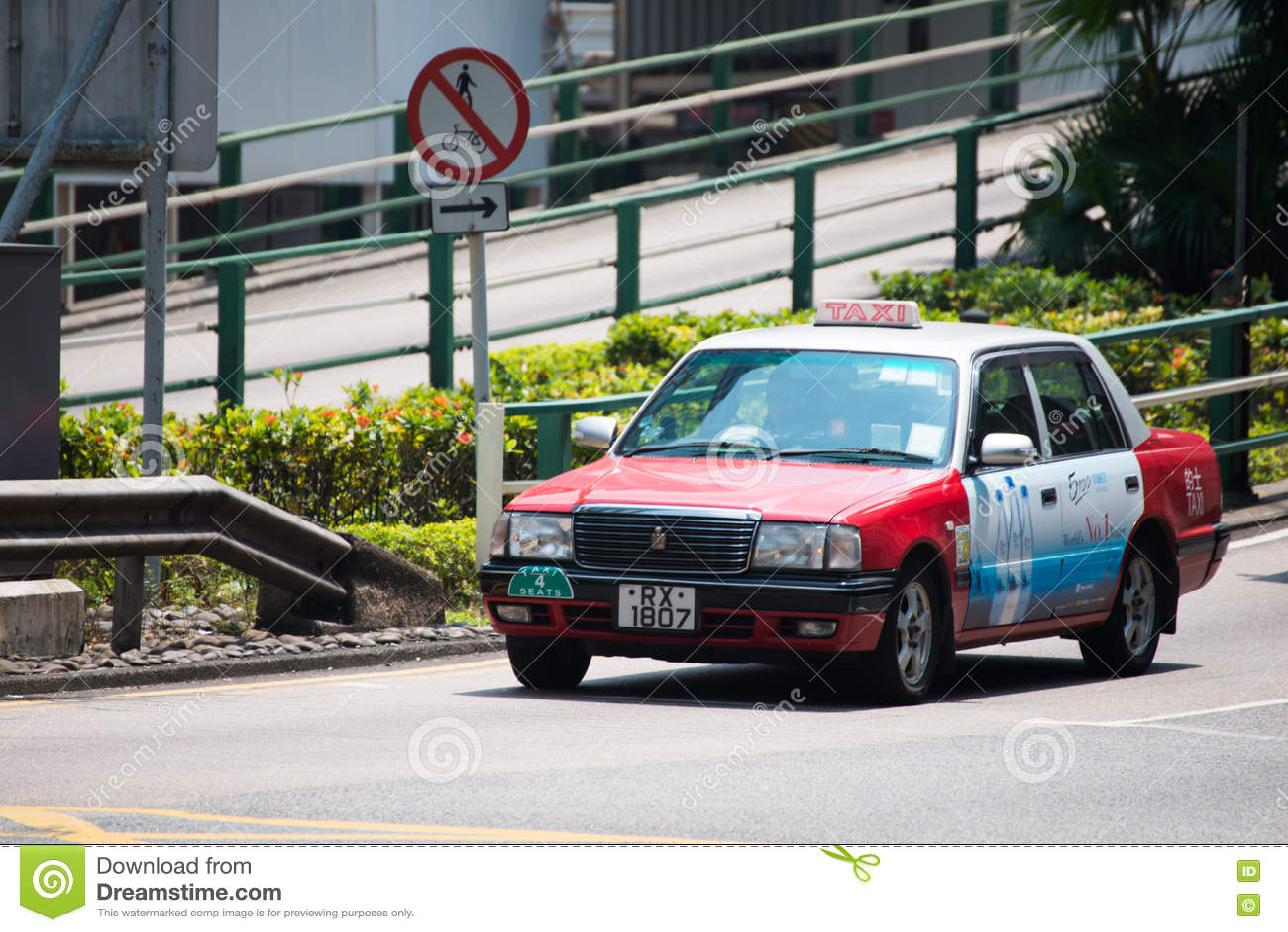Гонконг - 22-ое сентября 2016: Красное такси на дороге, ` Гонконга