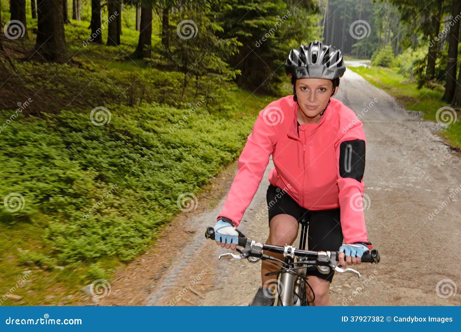 Гора женщины велосипед через дорогу леса