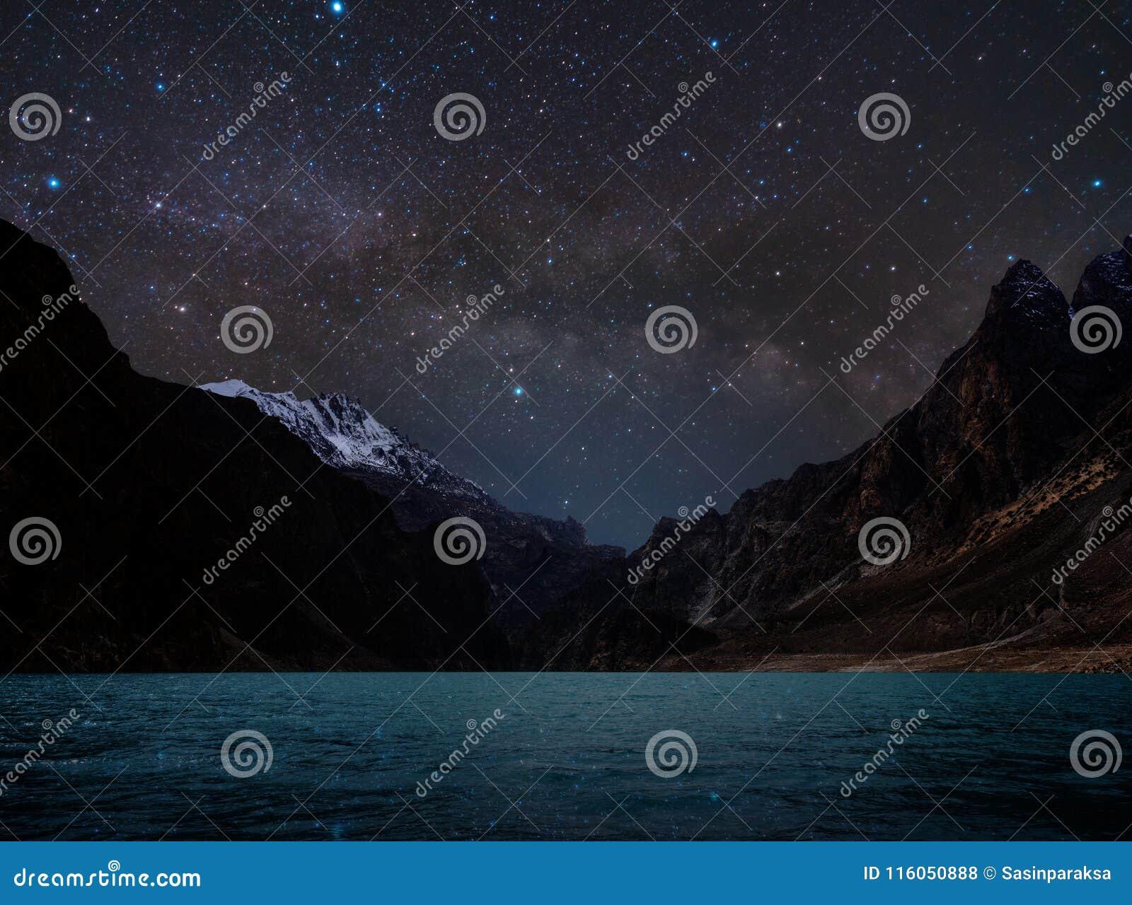 Гора ландшафта, силуэта ночи с водой на озере и небо вполне звезды с млечным путем