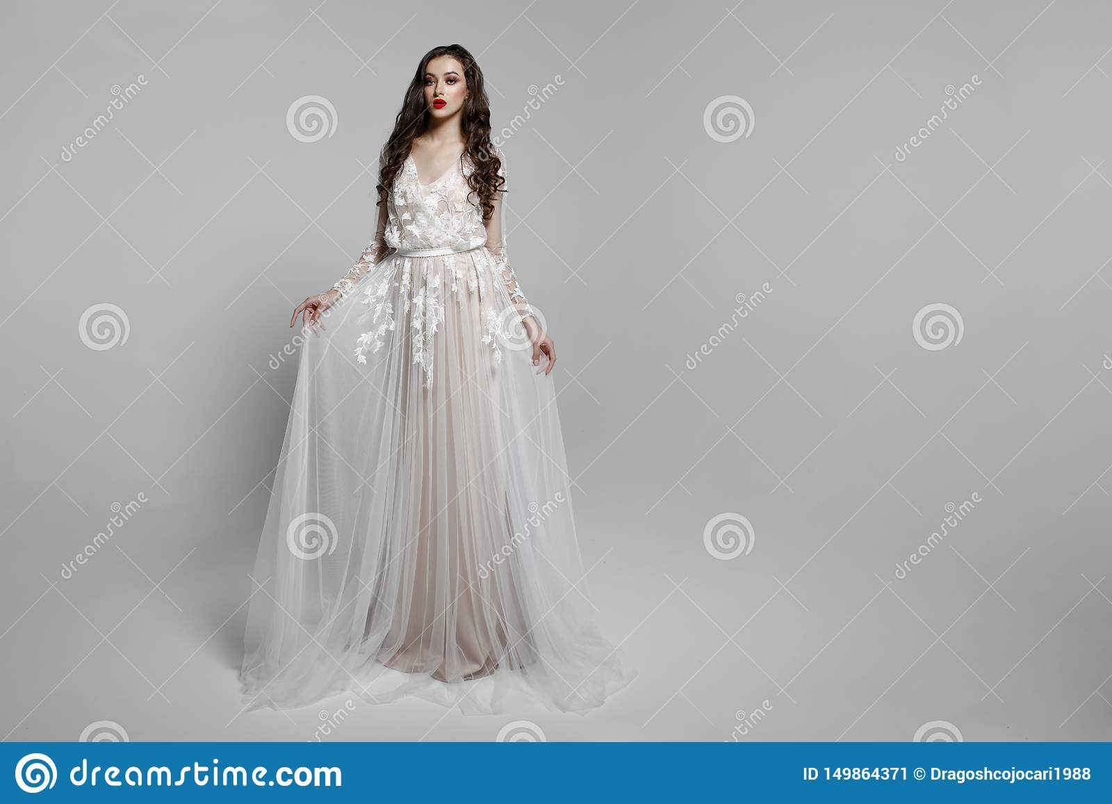 Горизонтальный взгляд красивой женской модели с длинными волосами, составляет в wendding платье, изолированном на белой предпосыл