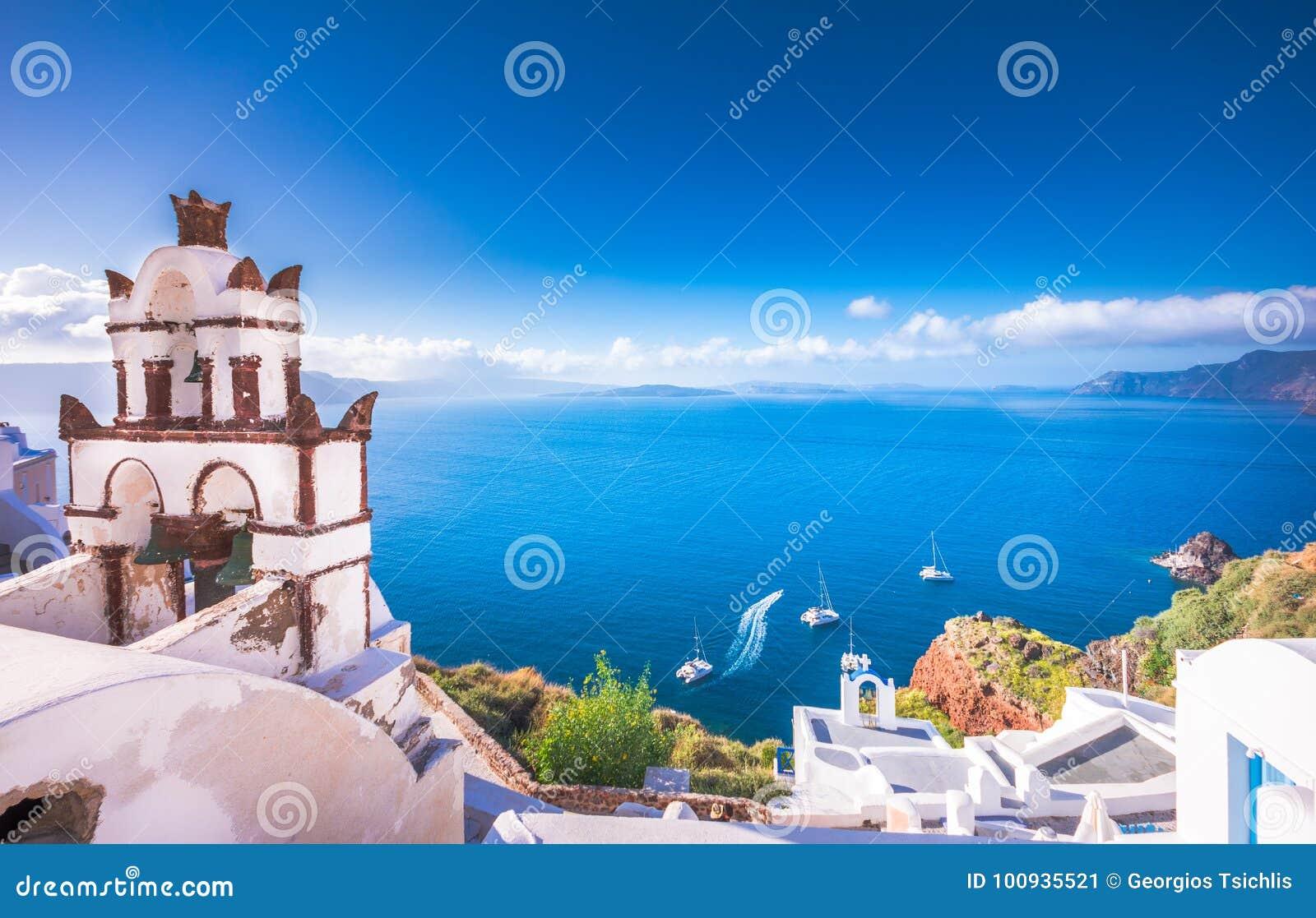 Городок Oia на острове Santorini, Греции Традиционные и известные дома и церков с голубыми куполами над кальдерой, Эгейским морем