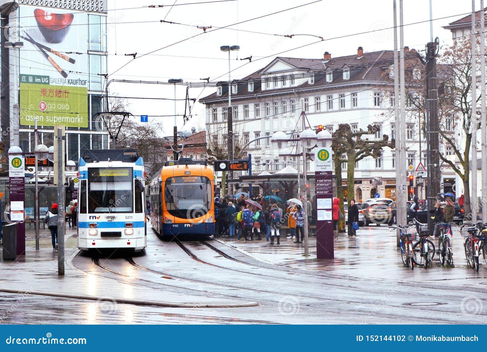"""Городской центр вызванное """"Bismarkplatz с железной дорогой города и соединение автобуса с много людей на дождливый день"""