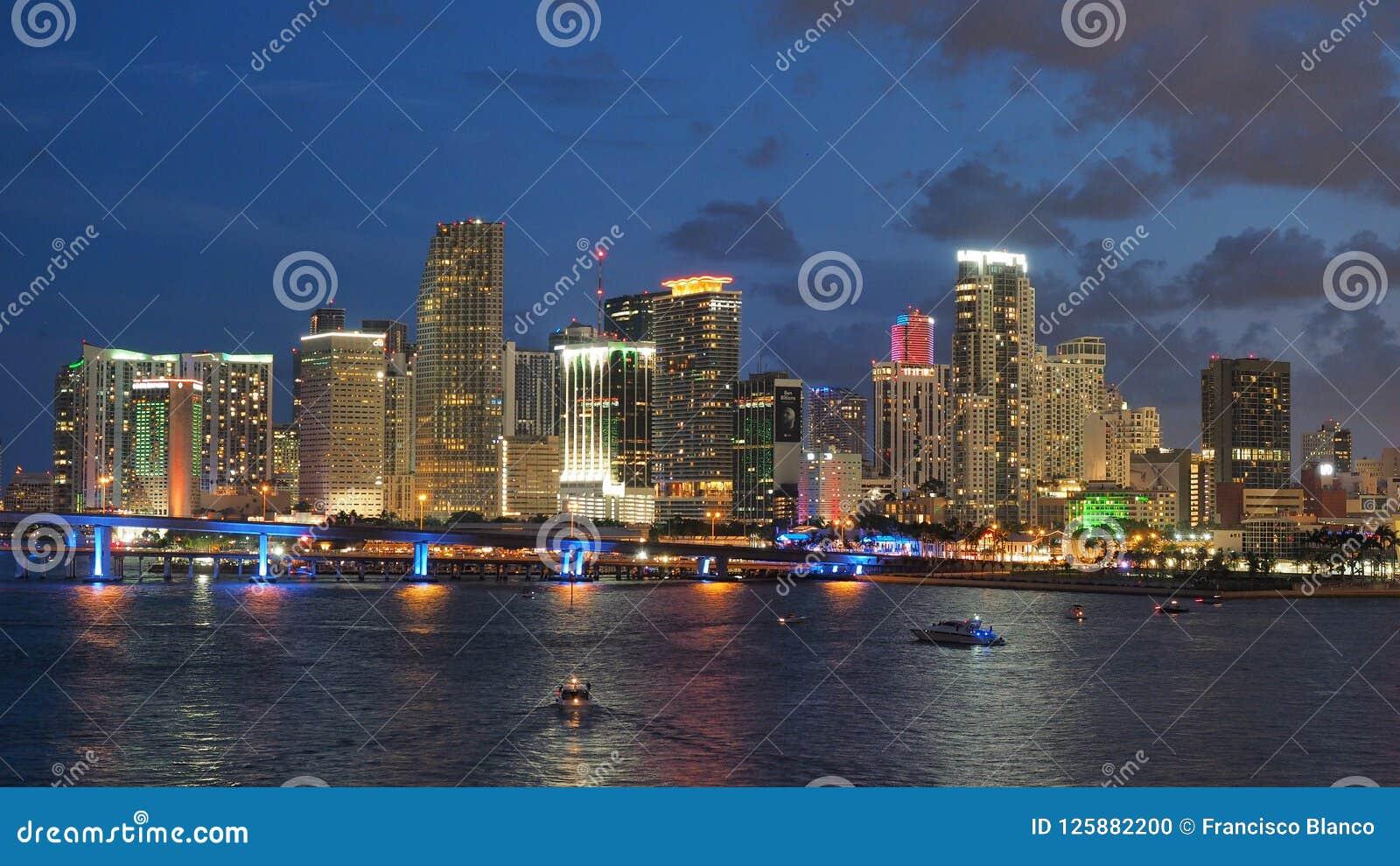 Город горизонта Майами отразил в заливе Biscayne на ноче