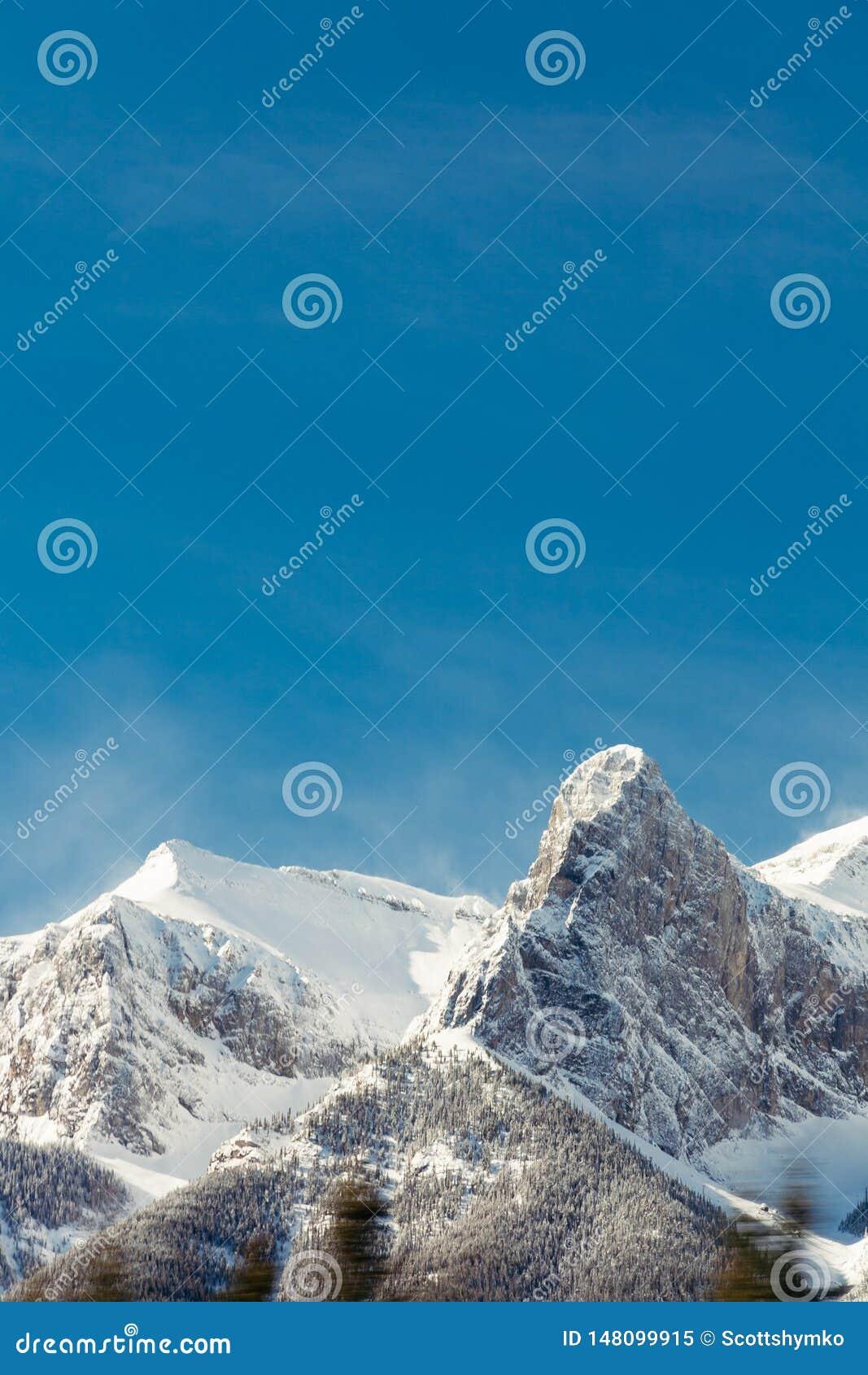 Горы Snowy скалистые и голубое небо, Banff, Альберта