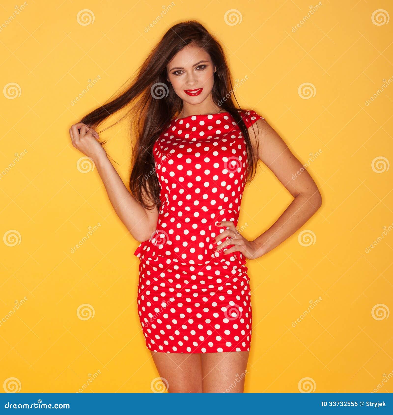 Горячая женщина нося красное платье точек польки