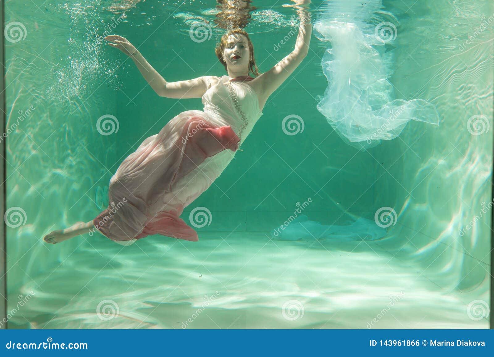 Горячая тонкая женщина представляя под водой в красивых одеждах самостоятельно в глубокой