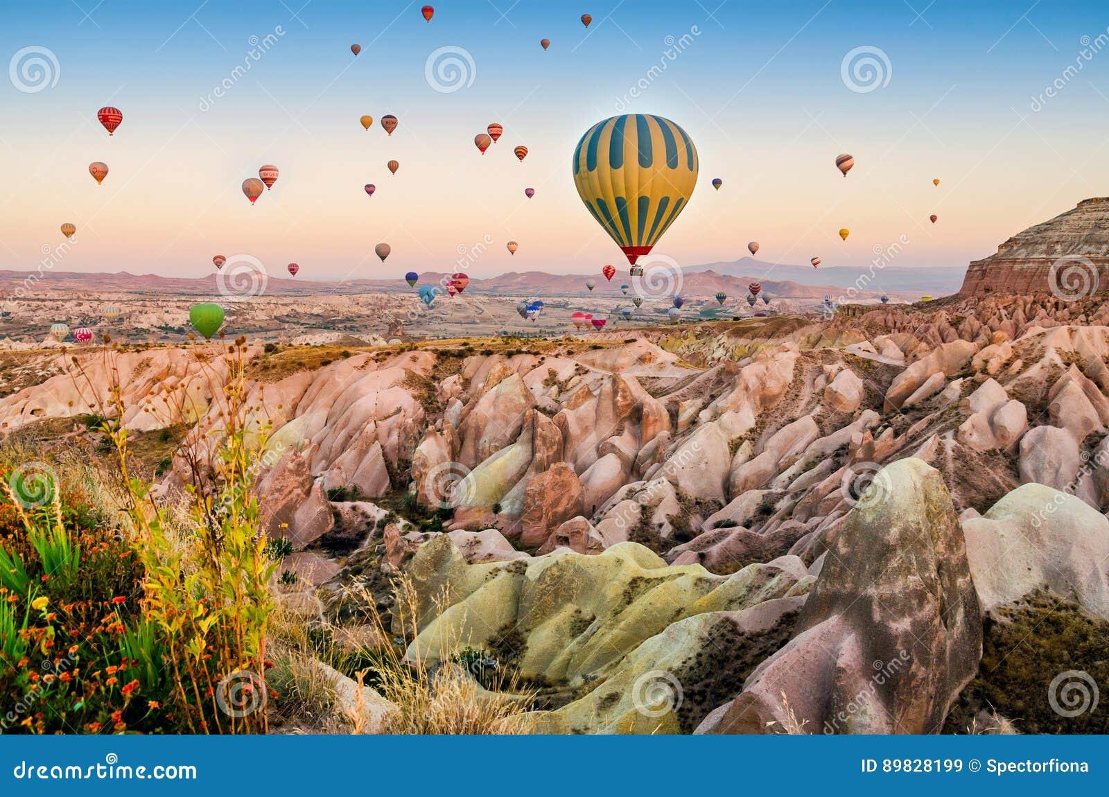 Горячий воздушный шар летая над ландшафтом утеса на Cappadocia Турции