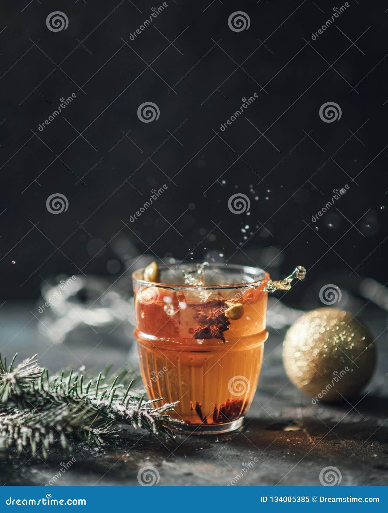 Горячий чай брызгает на темной предпосылке