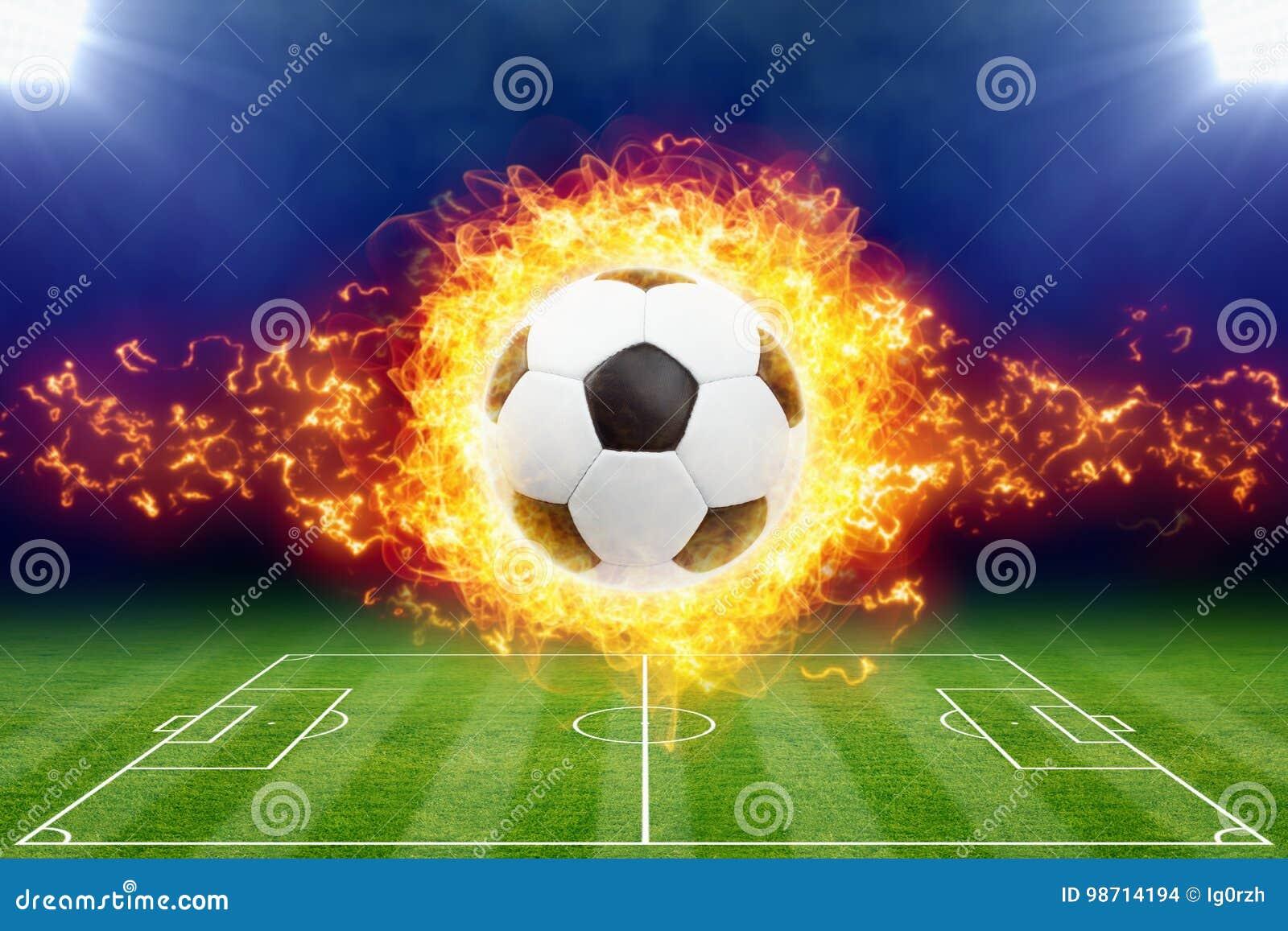 Горящий футбольный мяч над зеленым футбольным стадионом