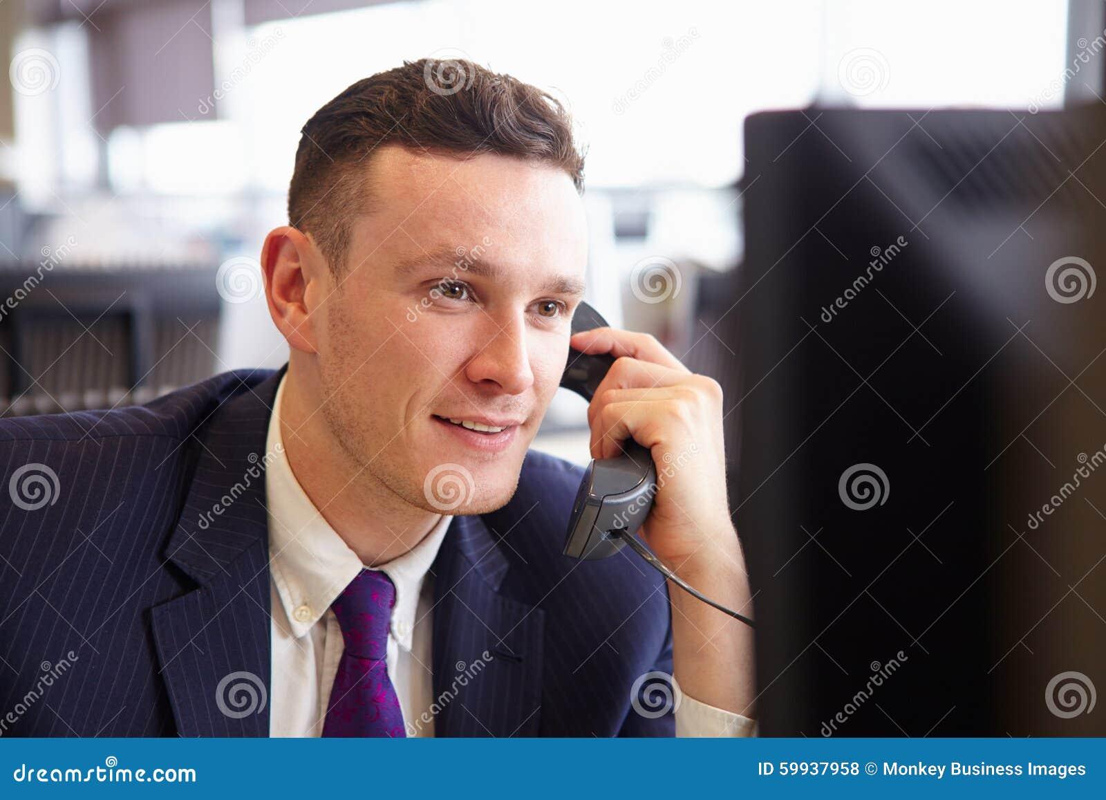 Головы и плечи молодого бизнесмена, используя телефон