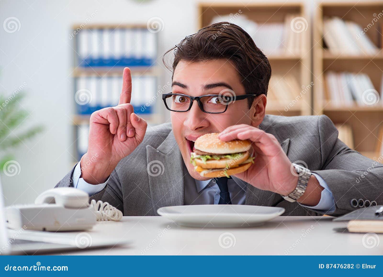 Голодный смешной бизнесмен есть сандвич высококалорийной вредной пищи