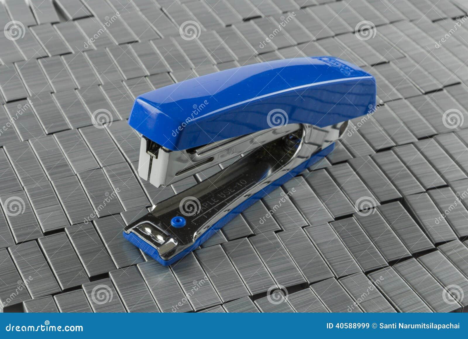 Голубой сшиватель на куче штапелей