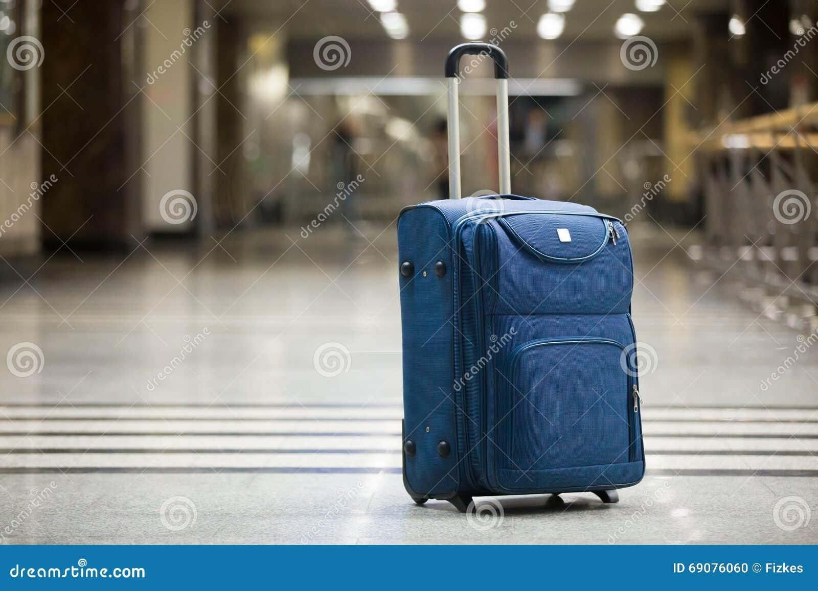 Голубой чемодан на авиапорте