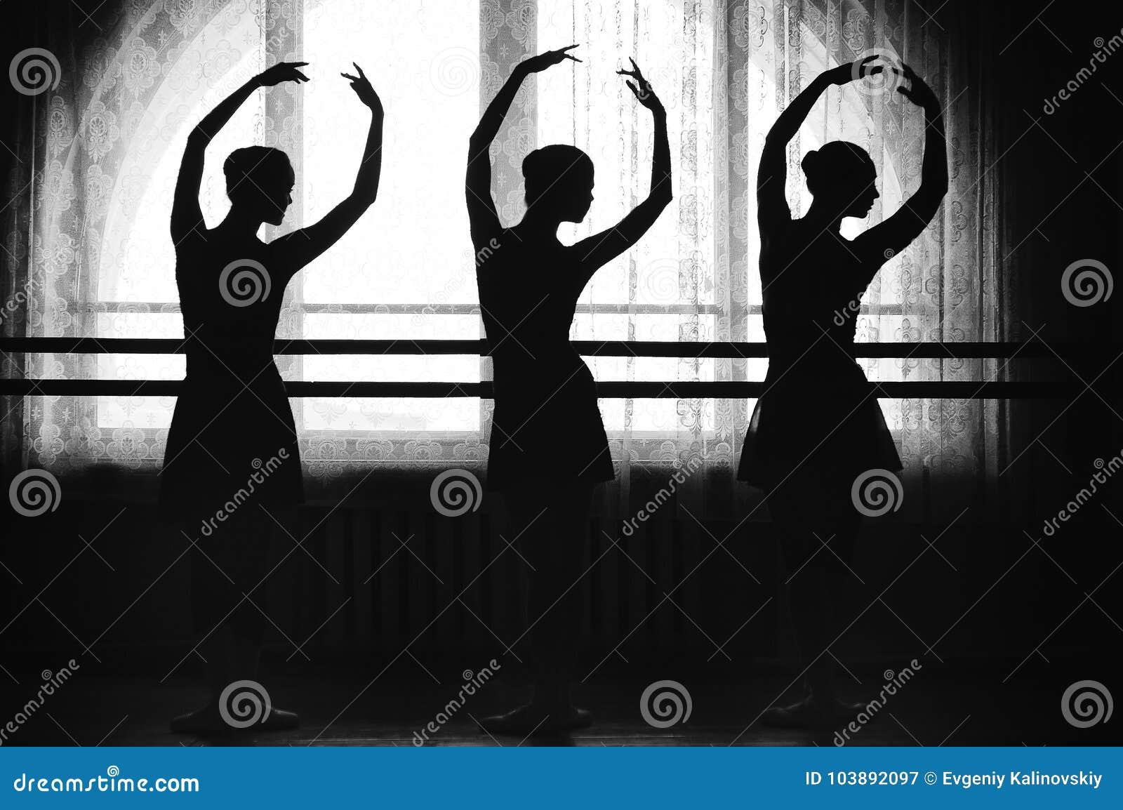 Грациозно силуэты балерин на предпосылке окна