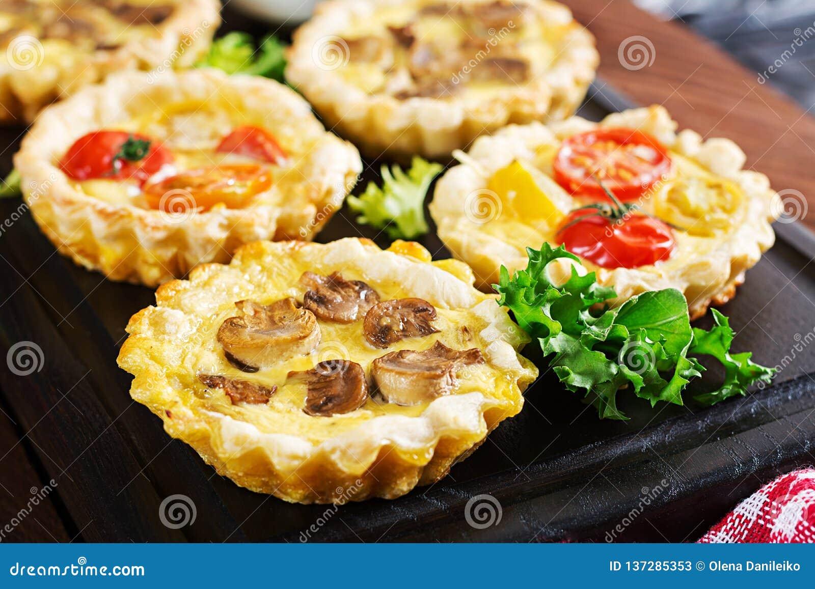Грибы, чеддер, tartlets томатов на деревянной предпосылке