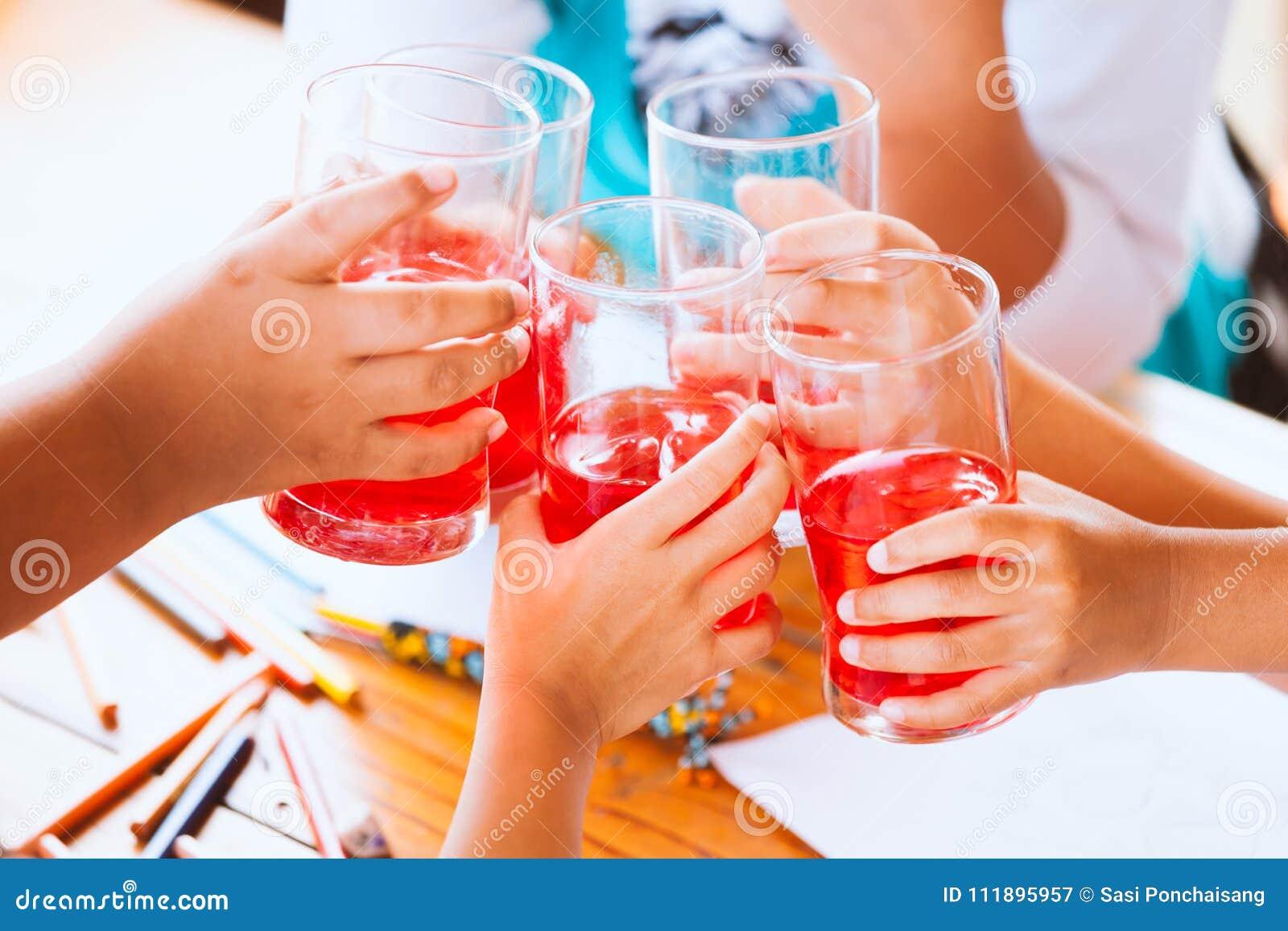 Группа в составе азиатские дети clinking стекла красной воды сока