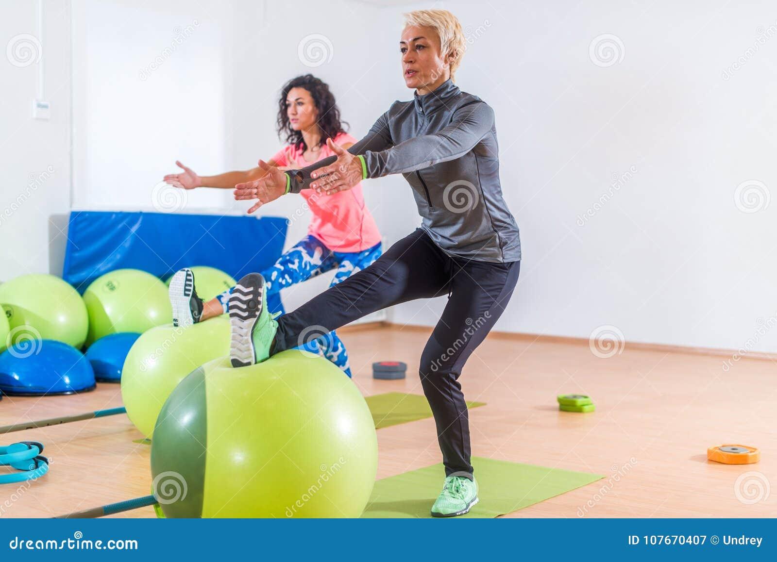 Группа в составе активные жизнерадостные sporty женщины делая одиночную ногу сидит на корточках с шариком баланса тренируя внутри