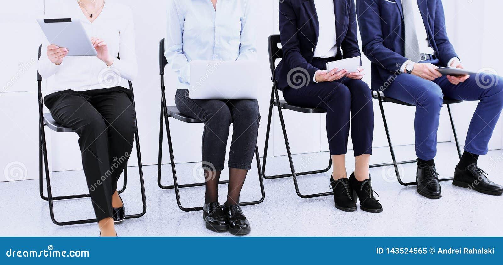 Группа в составе бизнесмены сидя в офисе и ждать собеседовании для приема на работу пока используя устройства, конец-вверх Конфер