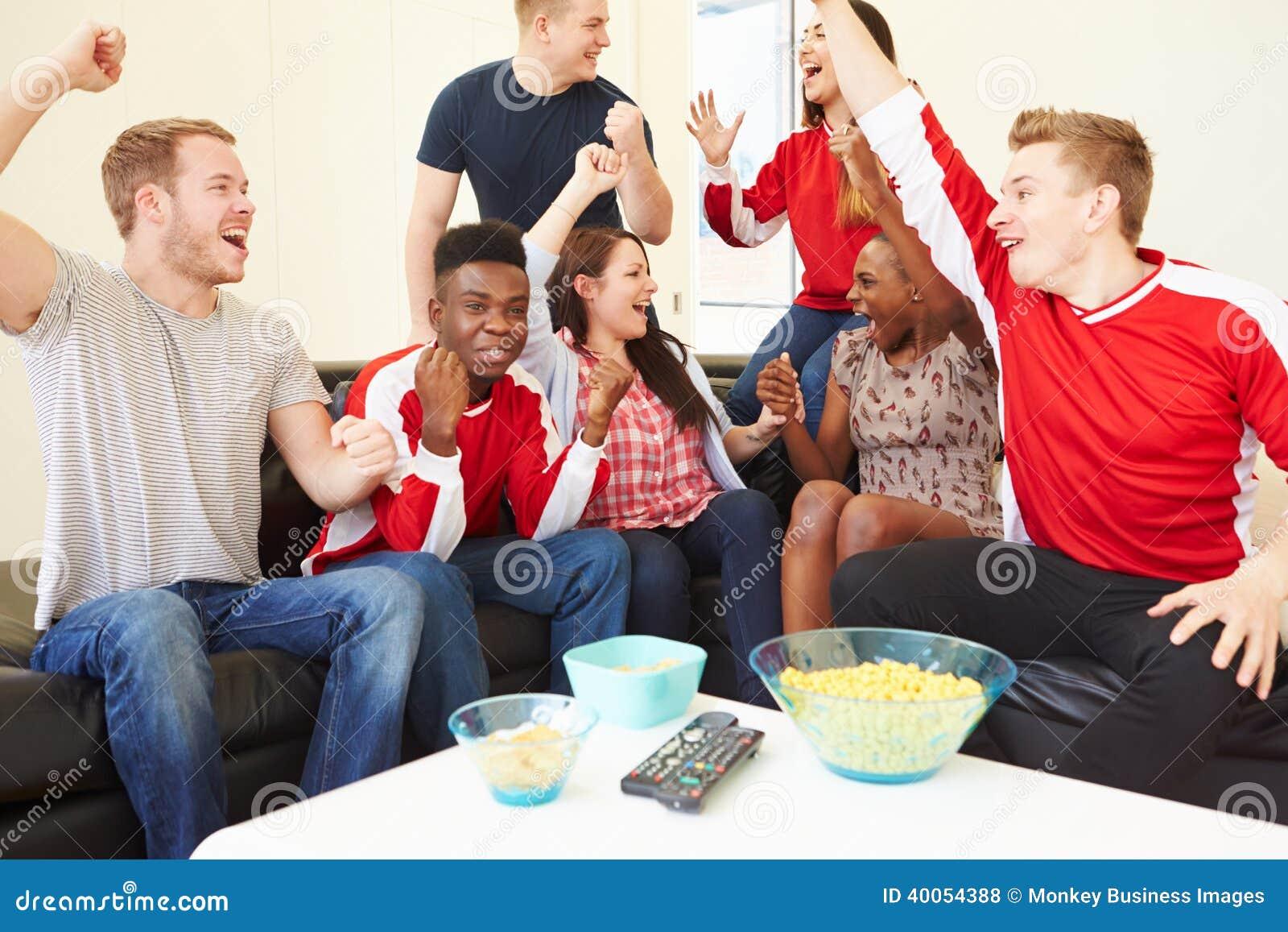 Группа в составе вентиляторы спорт смотря игру на ТВ дома