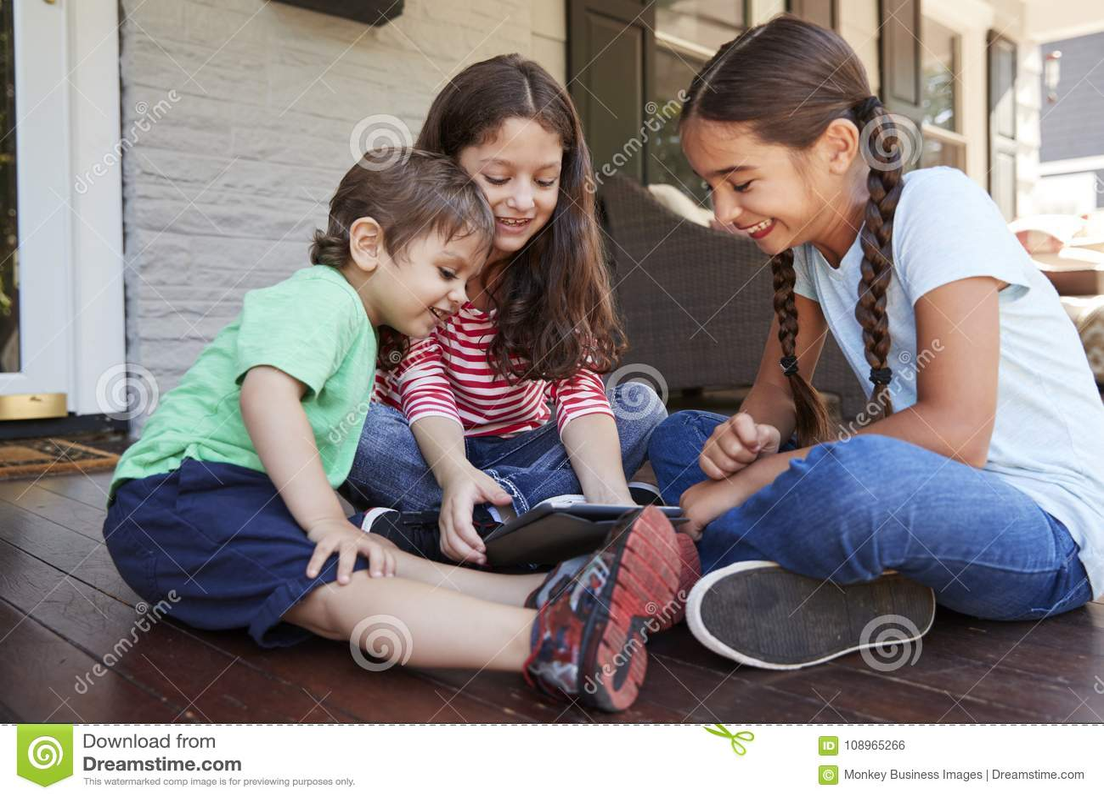 Группа в составе дети сидит на крылечке играя с таблеткой цифров