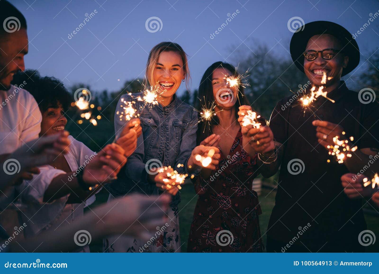 Группа в составе друзья наслаждаясь вне с бенгальскими огнями