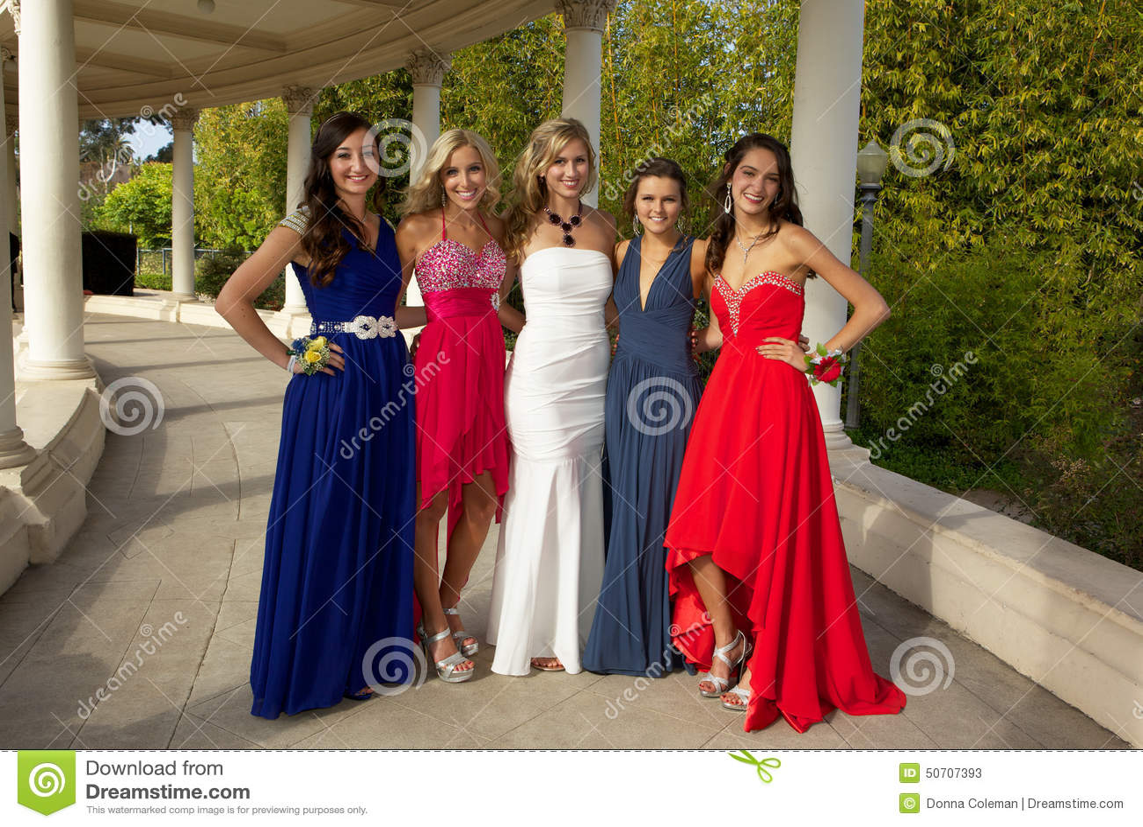 Группа в составе девочка-подростки представляя в их выпускном вечере одевает