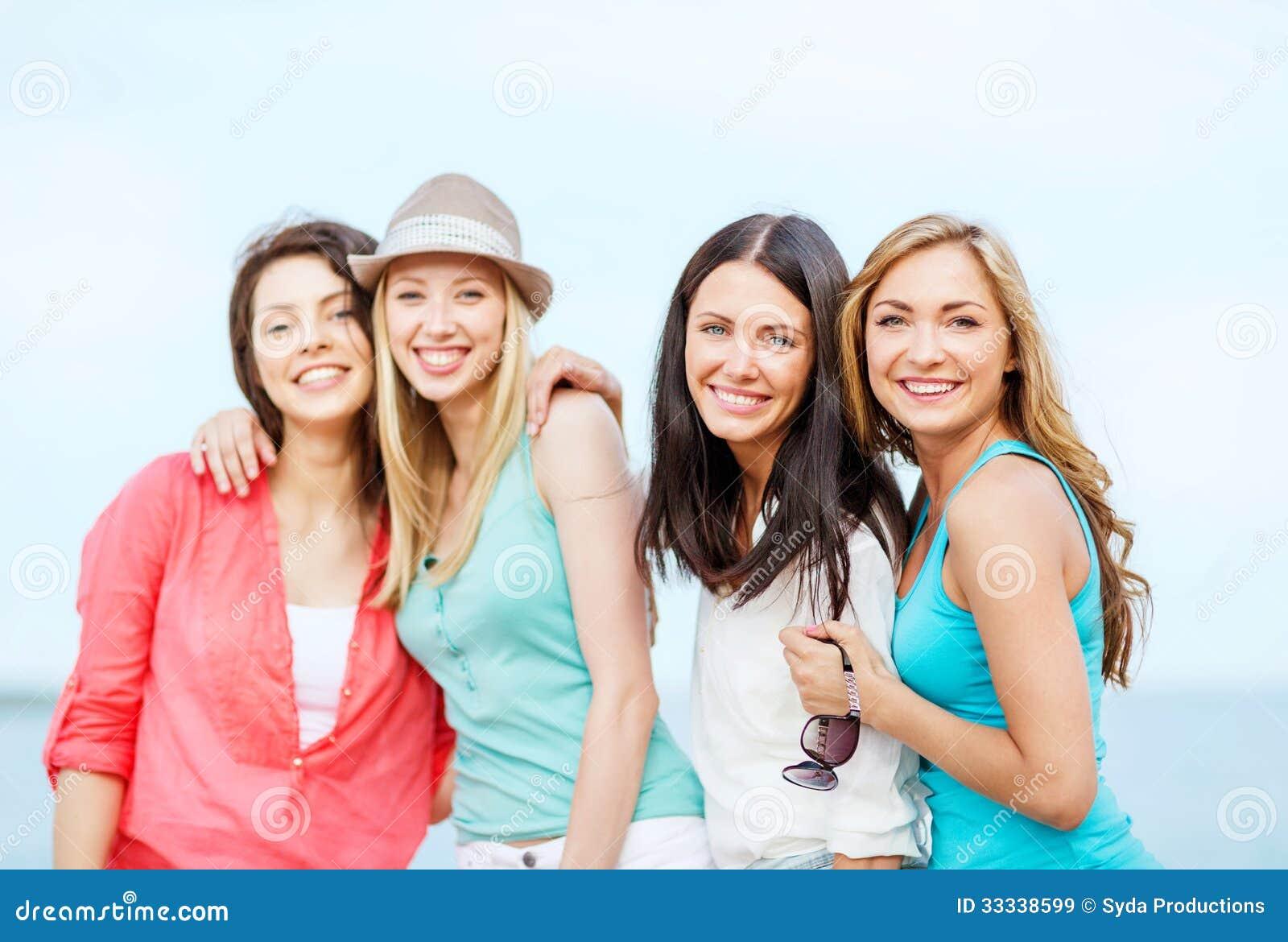 Группа в составе девушки охлаждая на пляже