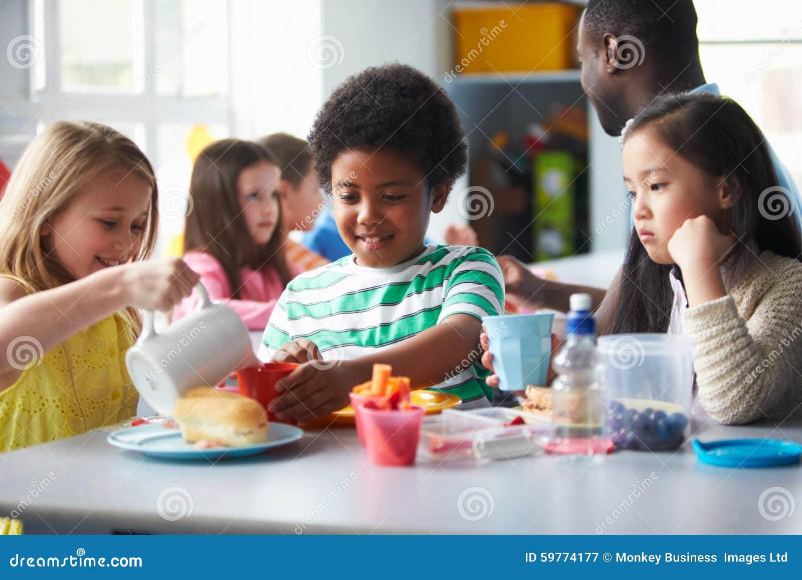Группа в составе дети есть обед в школьном кафетерии