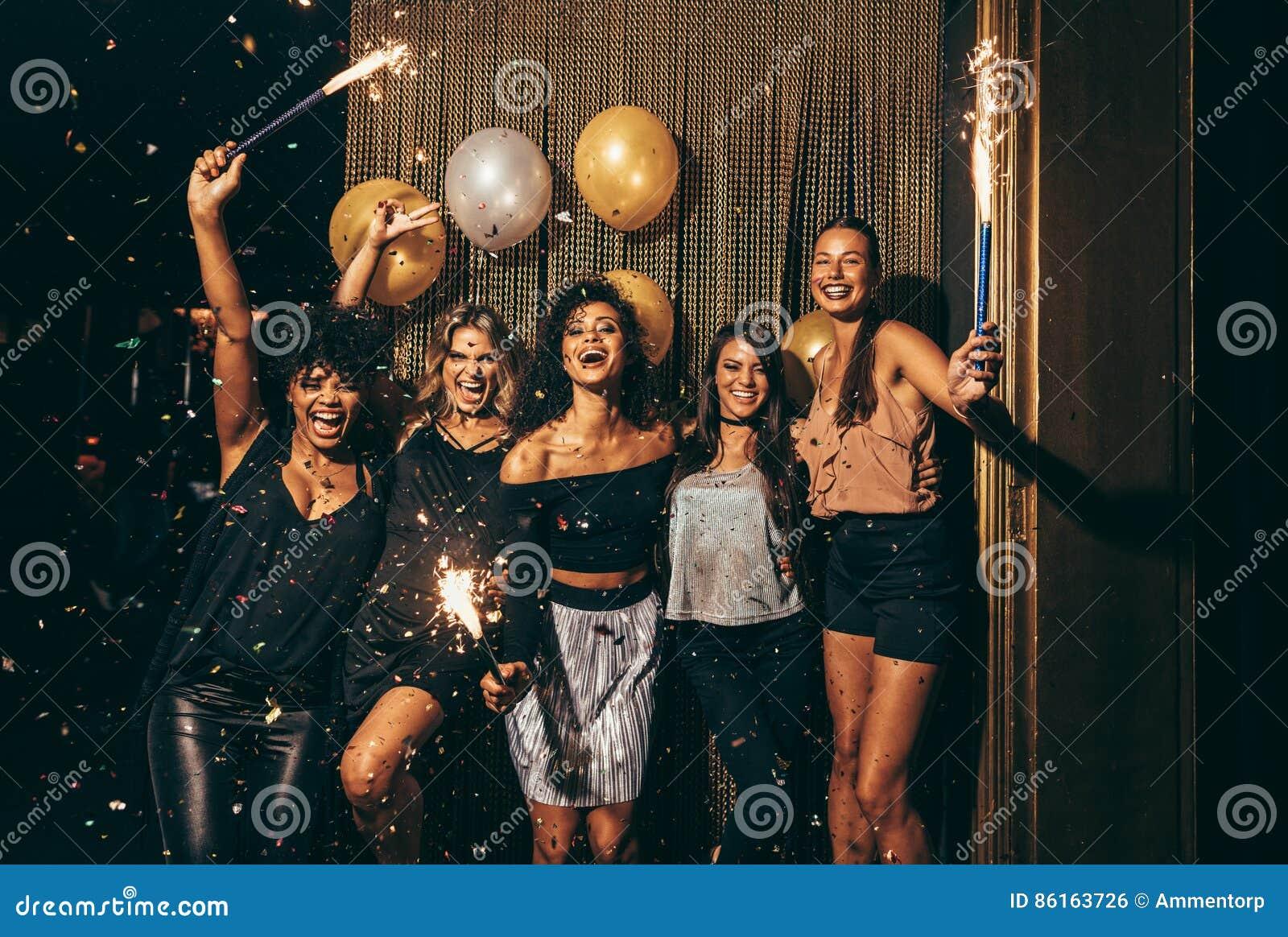 Группа в составе женщины имея партию на ночном клубе