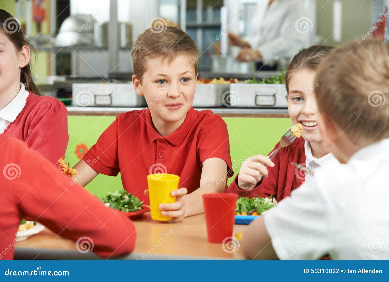 Группа в составе зрачки сидя на таблице в школьном кафетерии есть еду