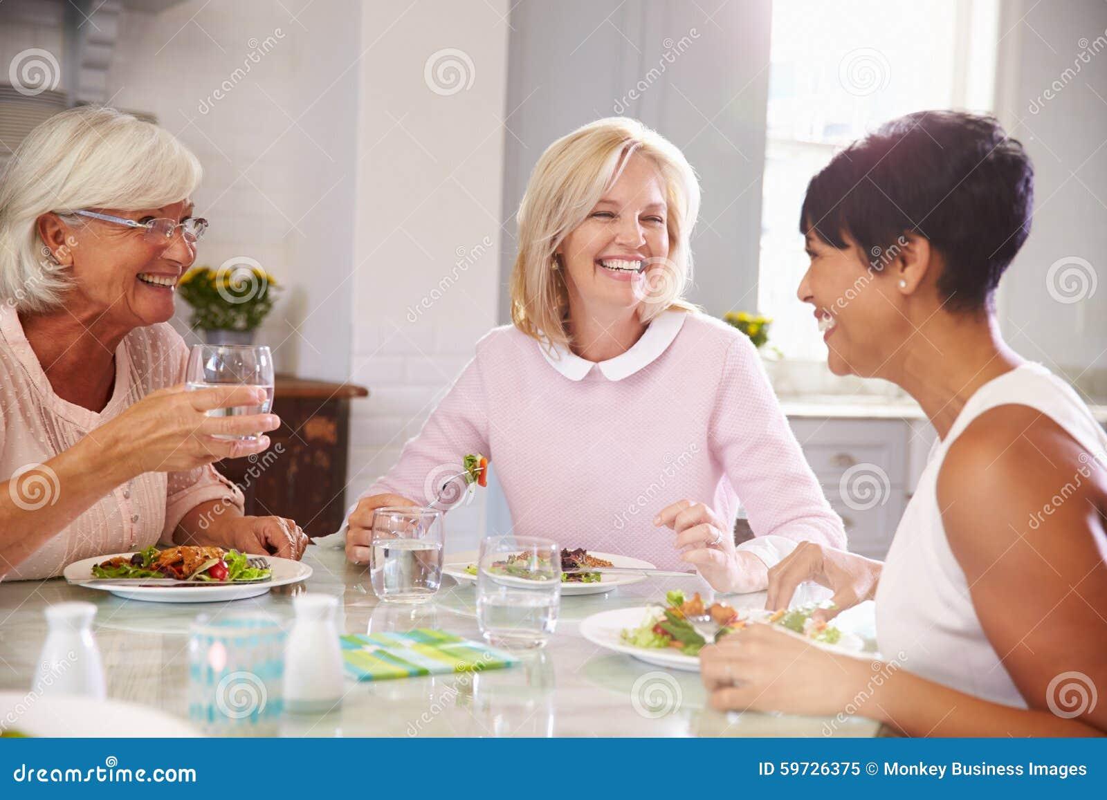 Группа в составе зрелые женские друзья наслаждаясь едой дома