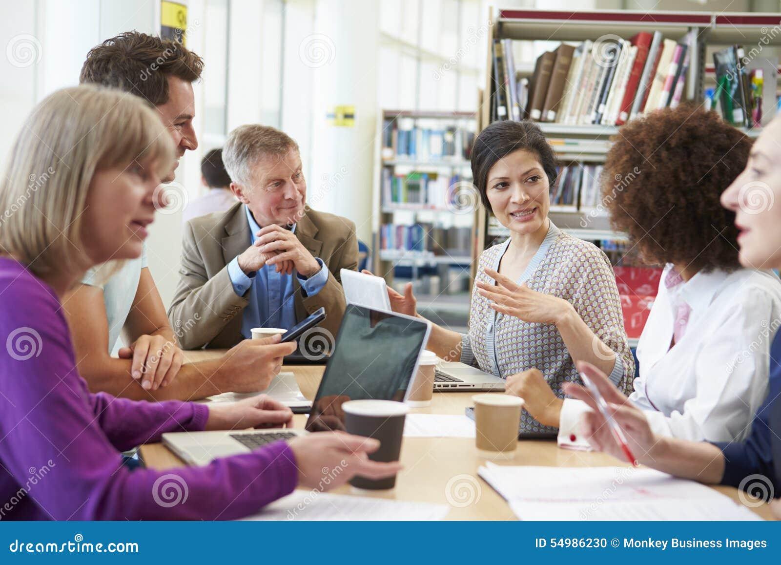 Группа в составе зрелые студенты сотрудничая на проекте в библиотеке