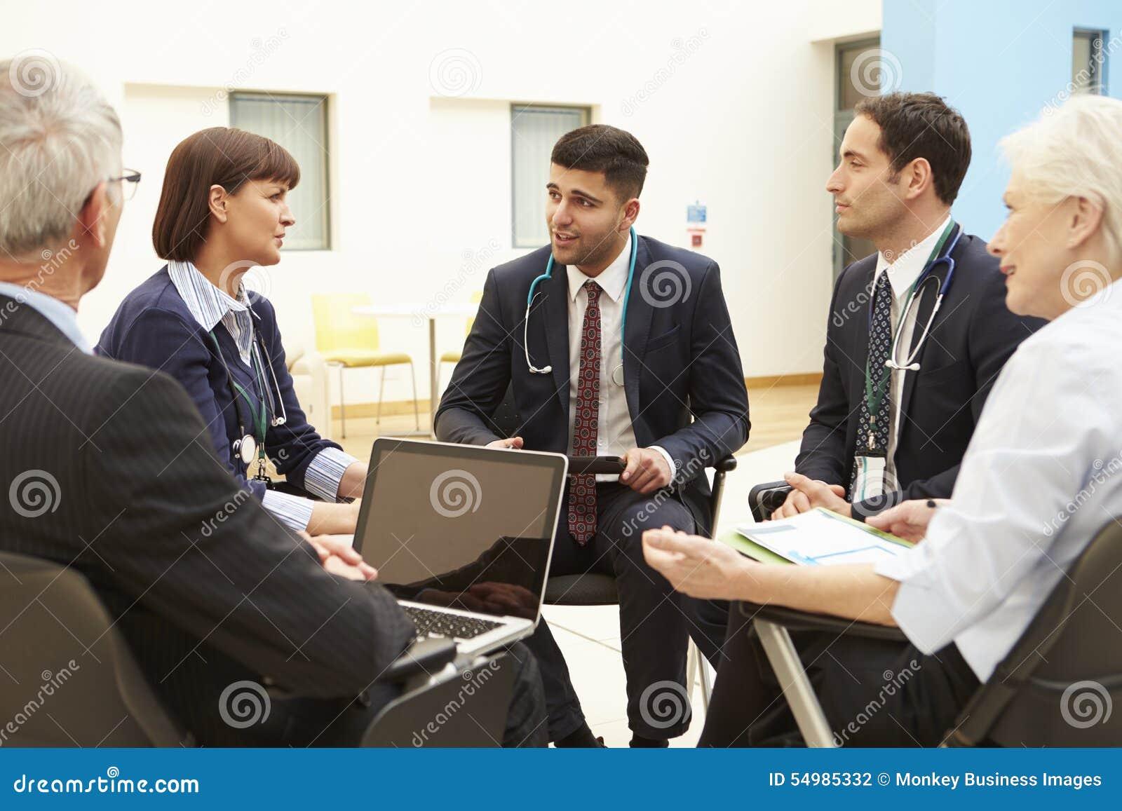 Группа в составе консультанты сидя на таблице в встрече больницы