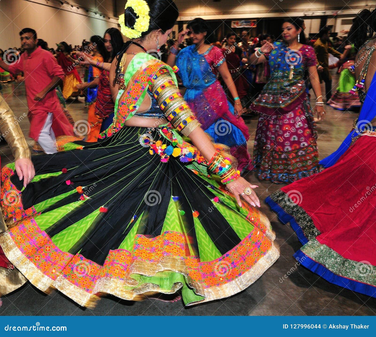 Группа в составе люди и женщины танцуют в действии Наслаждающся индусским фестивалем носить Navratri Garba традиционный уничтожьт