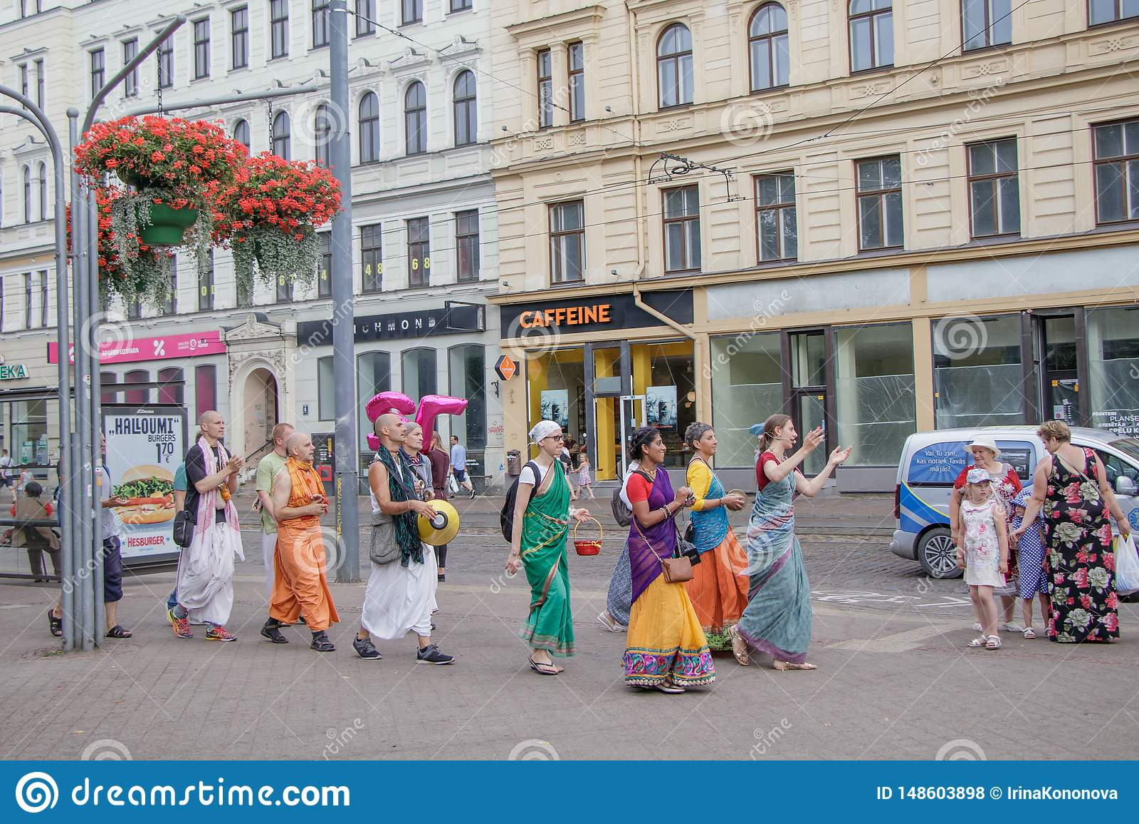 Группа в составе люди Krishna зайцев идя и поя в улицах Риги