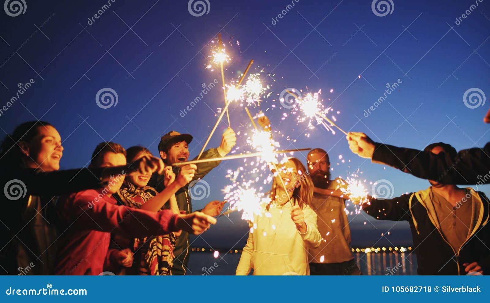 Группа в составе молодые друзья имея партию пляжа Друзья танцуя и празднуя с бенгальскими огнями в twilight заходе солнца