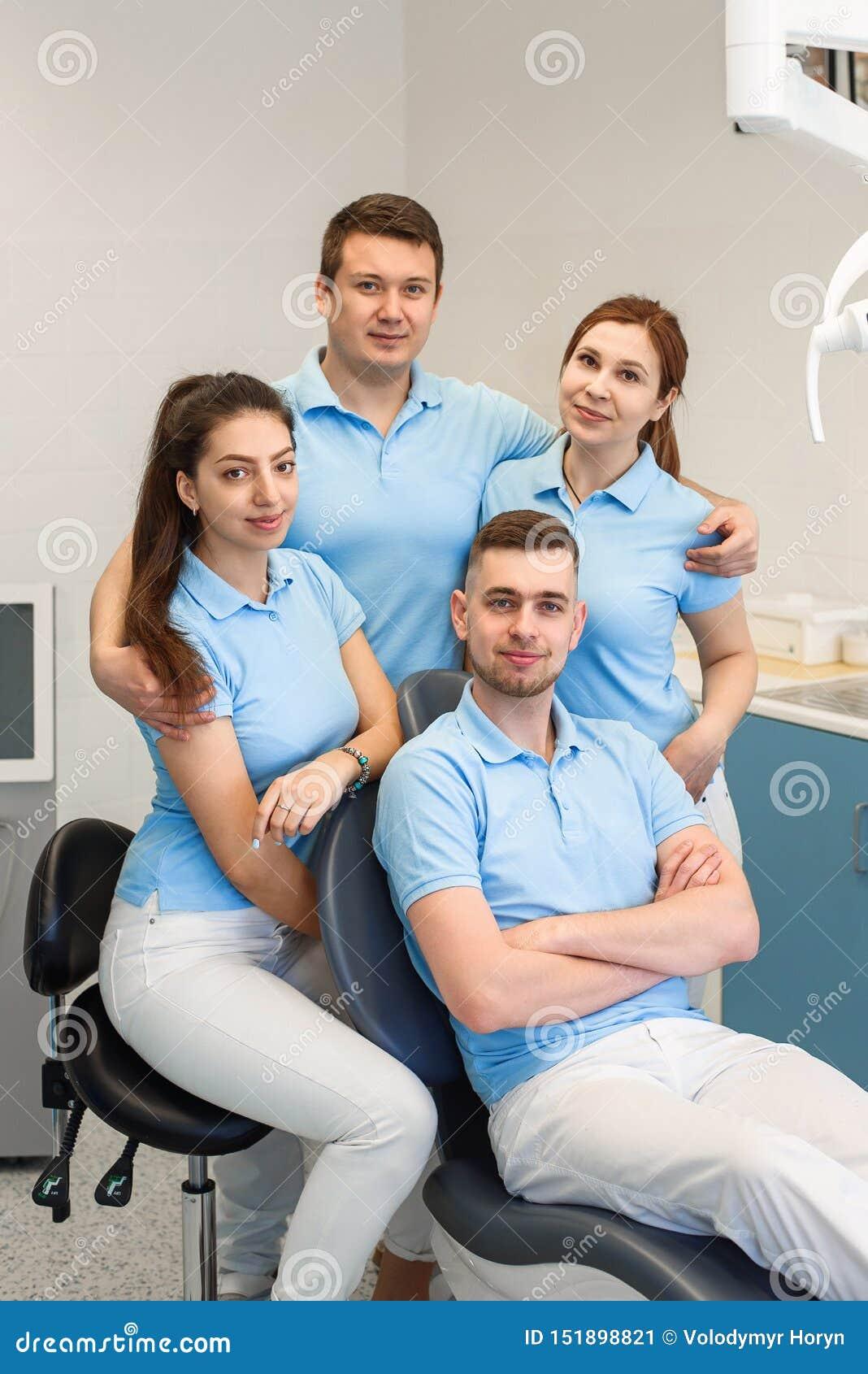 Группа в составе молодые и счастливые зубоврачебные доктора стоит около одина другого на зубоврачебной клинике Концепция сыгранно