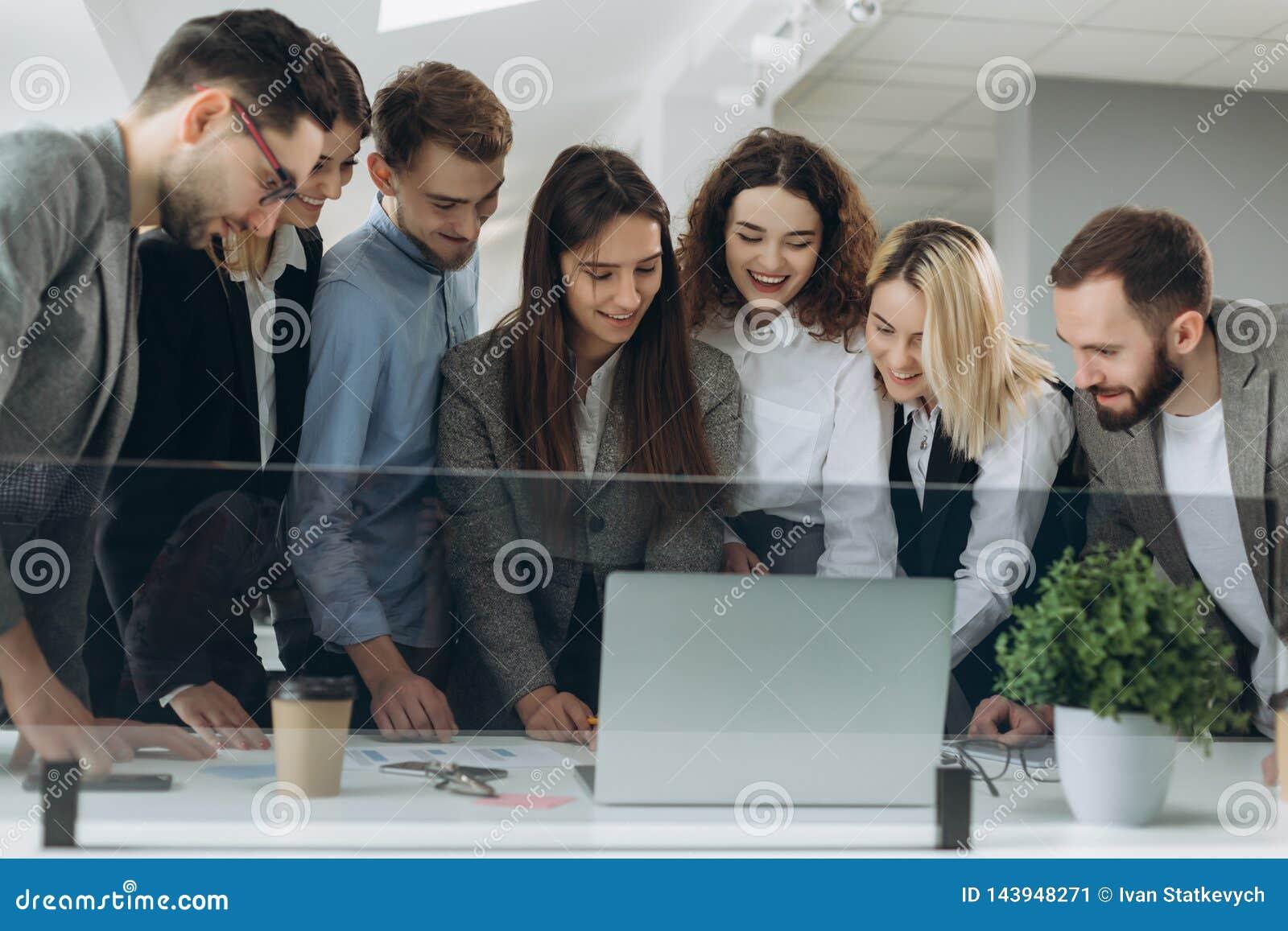 Работать совместно Группа в составе молодые современные люди в умной случайной носке обсуждая дело и усмехаясь в творческом офисе