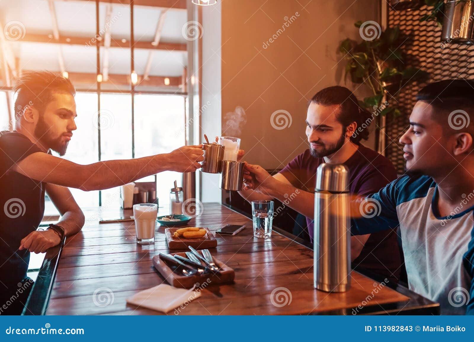 Группа в составе молодые человеки смешанной гонки clink стекла в Лаунж-баре Multiracial друзья имея потеху в кафе
