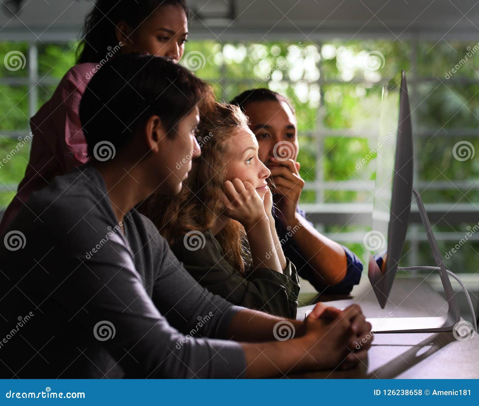 Группа в составе молодые businesspersons смотря умышленно на экране