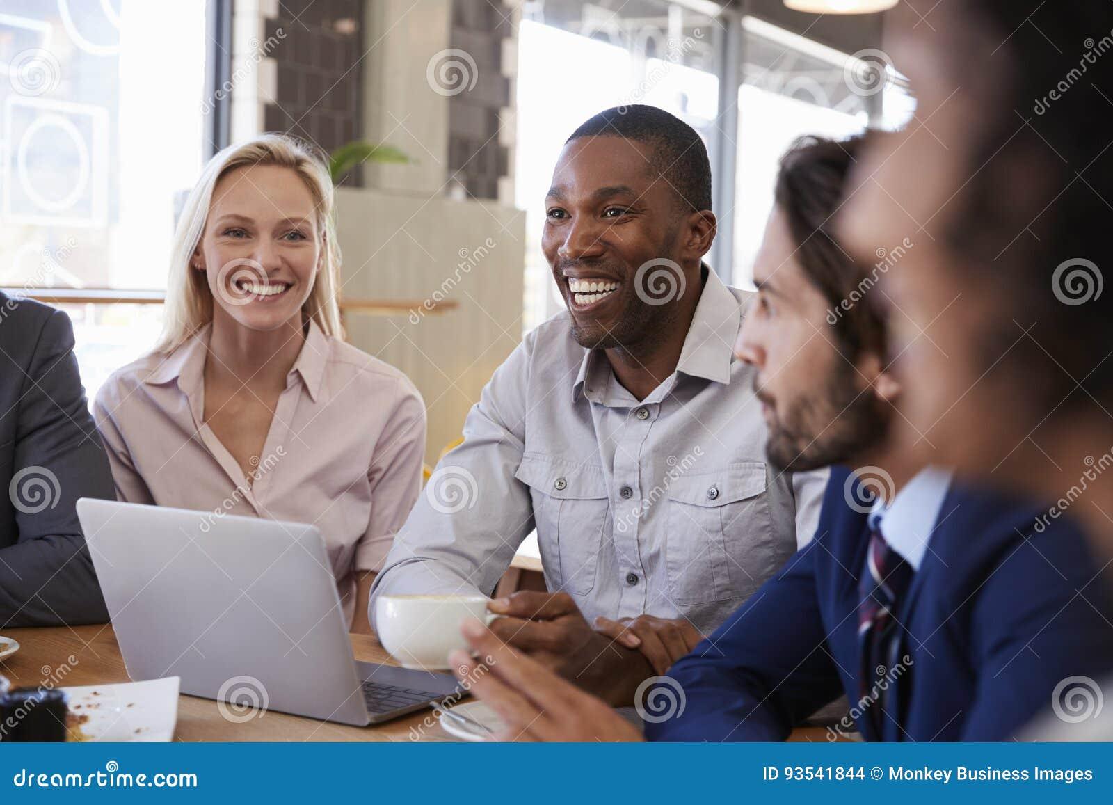Группа в составе предприниматели имея встречу в кофейне