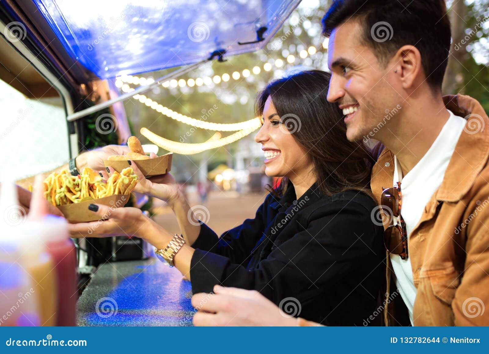 Группа в составе привлекательные молодые друзья выбирая и покупая разные виды фаст-фуда внутри ест рынок в улице
