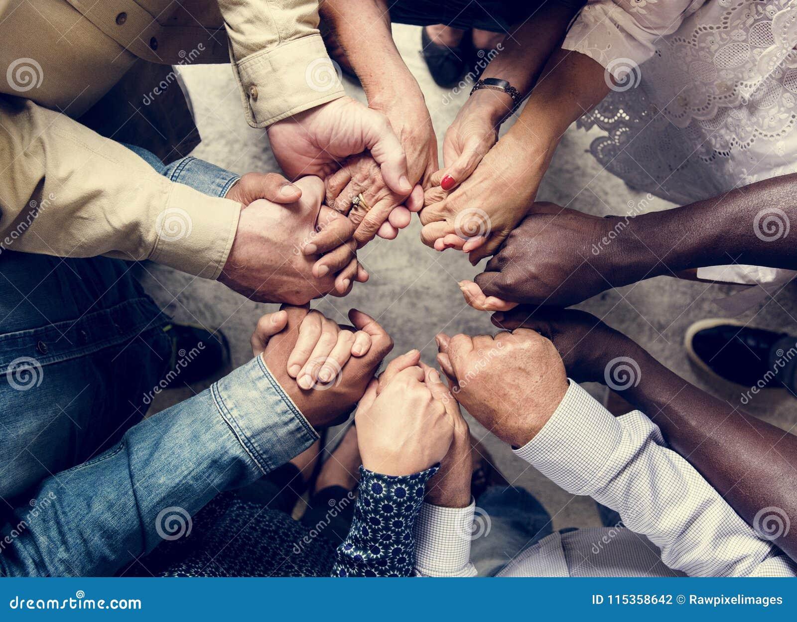 Группа в составе разнообразные руки держа один другого поддерживает совместно вид с воздуха сыгранности